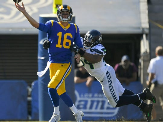 Los Angeles Rams quarterback Jared Goff, left, passes under pressure by Seattle Seahawks middle linebacker Bobby Wagner during the second half of an NFL football game Sunday, Oct. 8, 2017, in Los Angeles. (AP Photo/Mark J. Terrill)