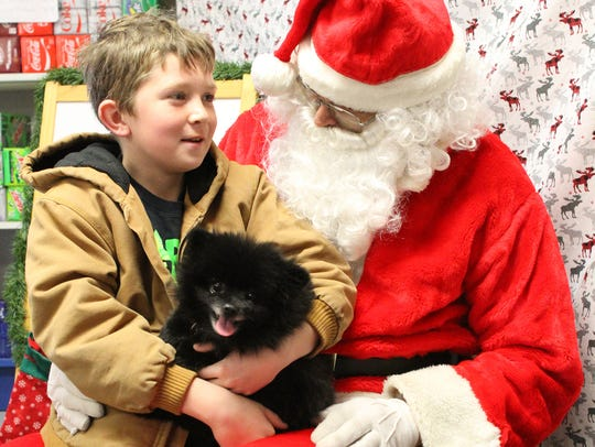 Aiden Huber and Mokie visit with Santa at the Ladora