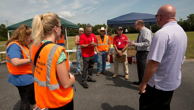 In this August 2014 file photo, KlaasKids Foundation National Search Director Brad Dennis, center, talks with a group of volunteers before they begin their search for a missing Pensacola man in the area off Dog Track Road and Blue Angel Parkway.