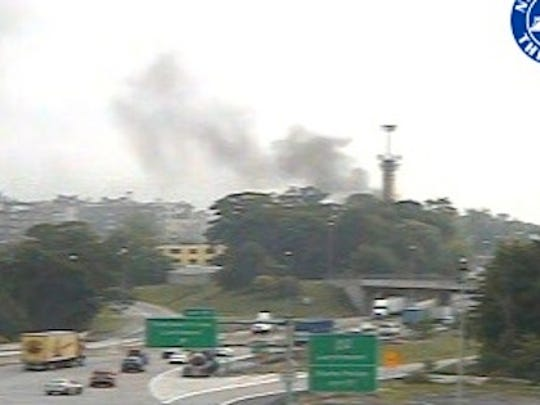 Smoke from an Interstate 95 tractor-trailer fire is visible in this Thruway Authority traffic camera image. The fire broke out southbound near the Chatsworth Avenue overpass in Larchmont, just north of the New Rochelle tolls, July 15, 2014.