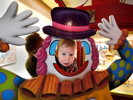 Thomas Lampe, 1, peers through a clown cutout at the