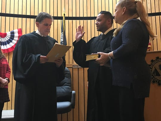 Jeremias E. Batista, center, takes his oath to become