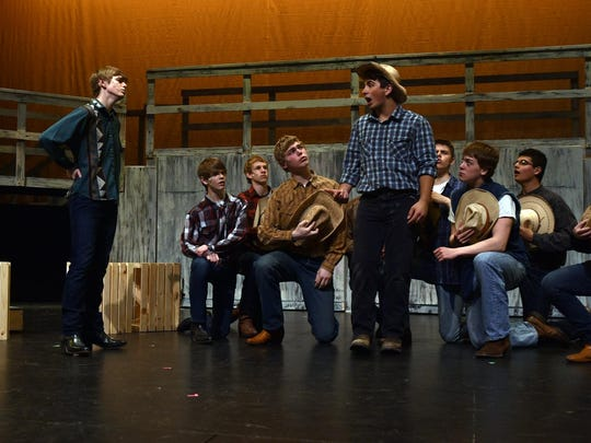 "Ren McCormack, played by Alec Hoffman, left, tries to convince Willard (Collin Strege, center) to dance to a down-home country band in the Gibraltar High School production of ""Footloose.''"