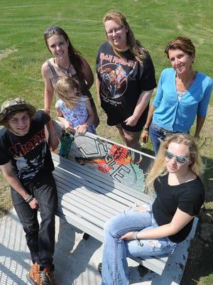 Blake Lieders' friends and family gather around one of five new benches installed at Adelaide Skate Park on Hickory Street in memory of him. From left, are: Lucas Urquhart, Blake's mother and sister Beata and Jillian Lieders, Robin Lemke, Ginger Reath, and Lynsi Langert.