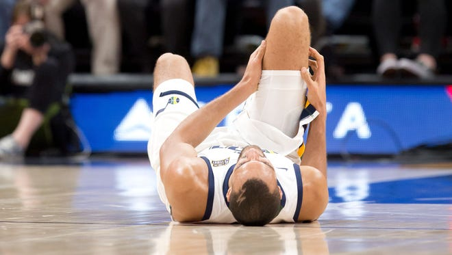 Utah Jazz center Rudy Gobert (27) lies on the court after injuring his knee during the second half against the Miami Heat at Vivint Smart Home Arena.