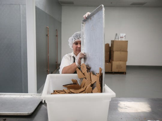 Graisy Romero, of Desert Hot Springs, pours broken pieces of toffee into a bin at  Brandini Toffee's new factory store in Rancho Mirage on Thursday, June 30, 2016.