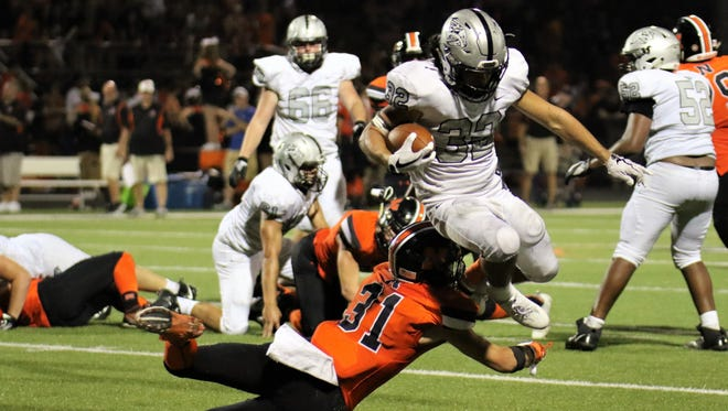 Northville's Brendan Rudolph (31) dives in an attempt to tackle Plymouth's elusive Carson Miller (32).