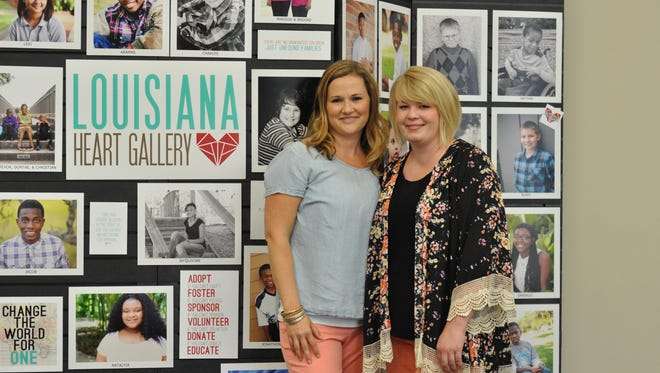 Adoption advocates Karley Duhon (left) and Andria Fontenot stand next to the Louisiana Heart Gallery, a project to showcase kids in foster care awaiting adoption.