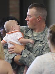 The 645th Regional Support Group will be deployed overseas sargent Logan Waltz holds his nephew Matthew Waltz five months old before a ceremony held at the Southfield Pavilion Saturday, in Southfield MI.