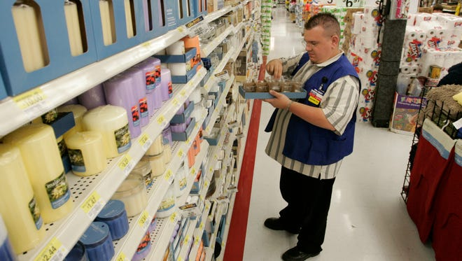 Dwayne Knechel, 31, of Souderton, PA straightens out the candle display at Walmart in Harleysville, PA.  Knechel is a department manager in furniture.