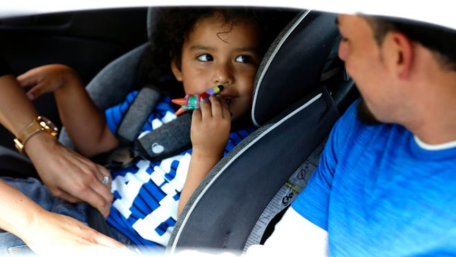 Ever Reyes Mejia's 3-year-old son smiles at him while being buckled into a car seat. The two Hondurans were reunited Tuesday, July 11, 2018,  in Grand Rapids, Mich., after being separated for three months.