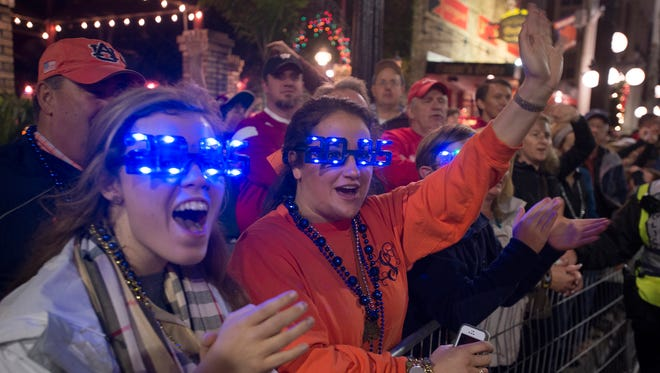 Lesley Ireland, Auburn alumnus, and Lauren Osborn, 16, cheer during the New Year Eve Parade in Ybor City and Pep Rally on Wednesday in Tampa, Fla.