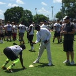 Purdue football coach Darrell Hazell times one of the campers in the shuttle run at Hillsboro High School in Nashville, Tennessee, on June 16, 2015.