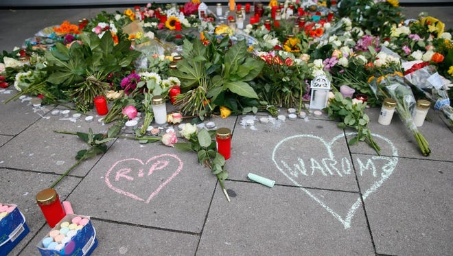 Flowers and candles are placed in front of a closed supermarket where a man attacked clients the day before in Hamburg.