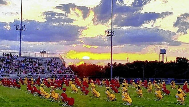 Big Walnut High School graduates practice social distancing as they sit on chairs spread over most of the school's football field during commencement under a setting sun July 25. The ceremony, originally scheduled May 16, was delayed more than two months as the district took steps to ensure safety during the COVID-19 coronavirus pandemic.