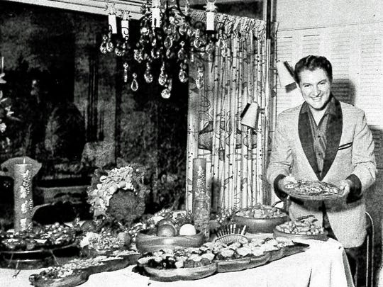 Liberace and the table of hors d'oeuvres he prepared for his sixty guests, Thanksgiving 1958.