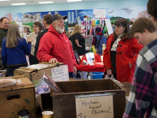 People shop the winter indoor Oshkosh Farmers Market at Merrill Middle School February 21, 2015.