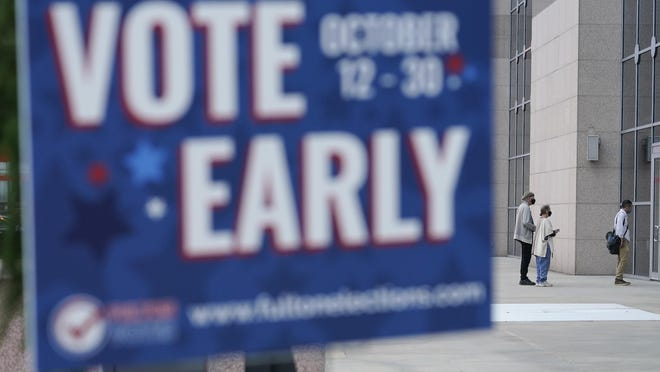 A line forms outside of the State Farm Arena for early voting on Monday, Oct. 12, 2020, in Atlanta.