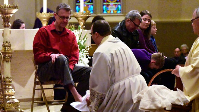 Rev. Michael Roemmele washes the feet of Ed Chimahusky of Fremont during an evening Mass of the Lord's Supper at St. Joseph Church in Fremont.