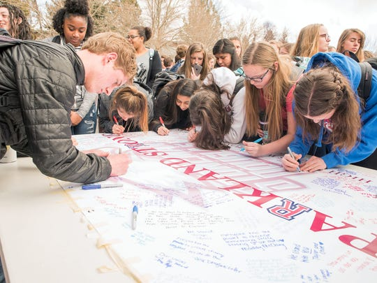 Reno High School students gather on the front steps and lawn to sign a Marjory Stoneman Douglas High School banner March 14, 2018 between 10 a.m. and 10:17 a.m.. About 300 students gathered for the 17 minutes to memoralize the 17 deaths in Florida.