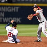 Apr 28, 2015; Atlanta, GA, USA; Washington Nationals shortstop Ian Desmond (20) tries to turn a double play over Atlanta Braves catcher Christian Bethancourt (27) during the ninth inning at Turner Field. The Nationals defeated the Braves 13-12.