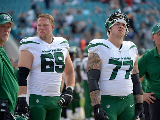 New York Jets offensive tackle Conor McDermott (69) and offensive guard Tom Compton (77) react on the sideline at the end of the second half of an NFL football game against the Jacksonville Jaguars Sunday, Oct. 27, 2019, in Jacksonville, Fla. (AP Photo/Phelan M. Ebenhack)