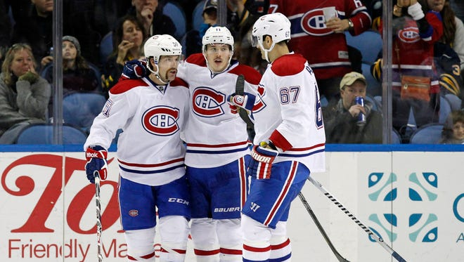 Montreal Canadiens center David Desharnais (51) celebrates his goal with right wing Brendan Gallagher (11) and left wing Max Pacioretty (67) during the second period against the Buffalo Sabres at First Niagara Center.