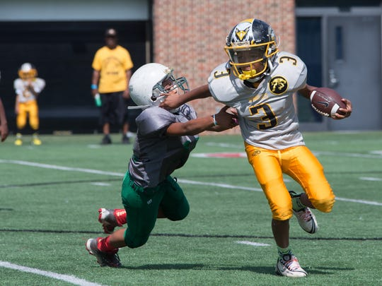 Seaonta Stewart, 9, of the Cincinnati Eagles, dodges a tackler in the first half of their game. More than 40 teams of kids gathered at the Sheakley Athletics Center for the 10th annual Peace Bowl Sunday July 31, 2016.