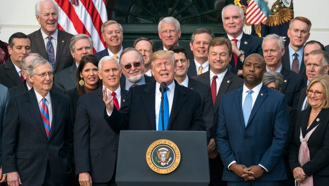 epa06400499 US President Donald J. Trump, joined by Republican members of the House and Senate, speaks about the passage of the Republican tax plan on the South Lawn of the White House in Washington, DC, USA 20 December 2017. The President is expected to sign the bill in January.  EPA-EFE/JIM LO SCALZO