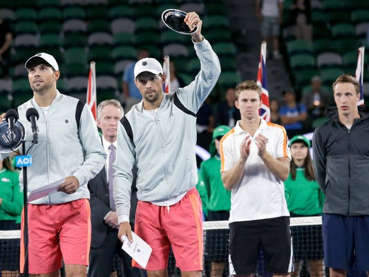 Bob, left, and Mike Bryan of the US wave after they finished runner-up in the men's doubles final against Finland's Henri Kontinen, right, and Australia's John Peers at the Australian Open tennis championships in Melbourne, Australia, Saturday, Jan. 28, 2017. (AP Photo/Aaron Favila)