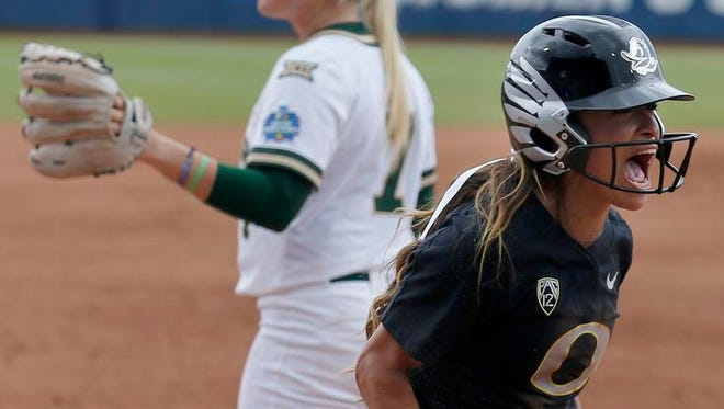 Oregon's Sammie Puentes (5) celebrates a score in front of Baylor's Gia Rodoni (7) in the second inning during the Women's College World Series softball game in Oklahoma City, Saturday, June 3, 2017. (Sarah Phipps/The Oklahoman via AP)