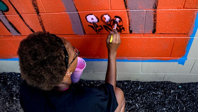 Layla Thompson, 14, carefully paints flowers on a mural at YES Club that highlights the importance of solar energy, including the solar panels on the roof of their clubhouse in downtown Newark.