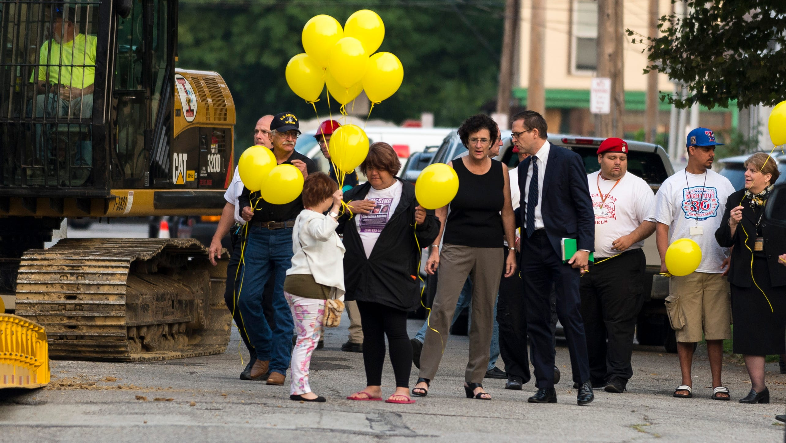 Michelle Knight hands out yellow balloons outside the home to represent other missing people waiting to be found. The three women were freed May 6 when one alerted a neighbor.