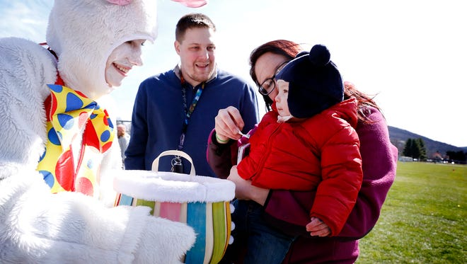 Parents Cameron Stanton and Emily Marois cheer on 8-month-old Sawyer Stanton as he receives a bracelet from the Easter bunny at Chapel Park in Southport Saturday.
