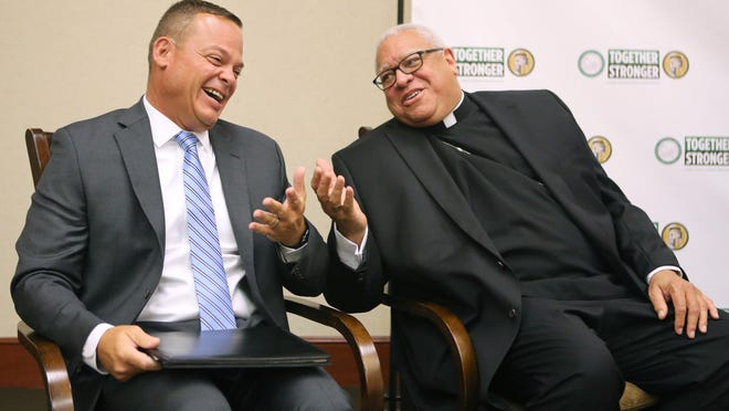 Daniel A. Gravo (left) and George V. Murry, bishop of the Youngstown Diocese, share a lighter moment during a press conference at Walsh University where Gravo was named president of Stark County Catholic Schools in 2017.