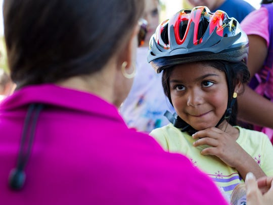 Jackie Gallardo, 5, gets fitted for a new helmet by