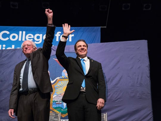 New York Gov. Andrew Cuomo, right and Vermont Sen. Bernie Sanders wave at the audience as they arrive onstage at an event at LaGuardia Community College, Tuesday, Jan. 3, 2017, in New York.  (AP Photo/Mary Altaffer)