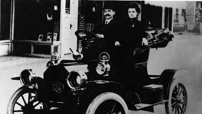 O.C. Bernard and his wife in their first new car, a 1907 REO, in front of their studio at 609 E. San Antonio St.