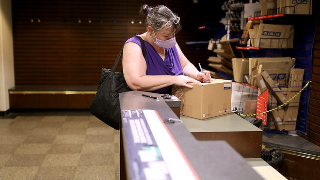 Karen Cobb of Quincy fills out the address for her older sister's group home before sending her a package of hand santizer at the Quincy Center post office.