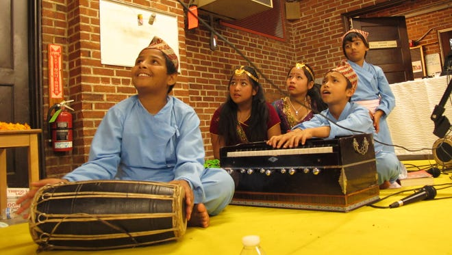 Sanjit Tiwari, 12, at left, joins his friends in watching (and occasionally accompanying) fellow Nepalis perform Saturday at the Dushain festival in Burlington.