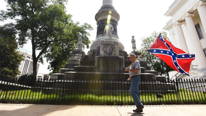 Mike Williams, adjutant for the Sons of Confederate Veterans in the state of Alabama, carries a confederate flag past the Confederate Memorial on the state capitol grounds in Montgomery, Ala, after four flags were removed from the memorial on Wednesday June 24, 2015.