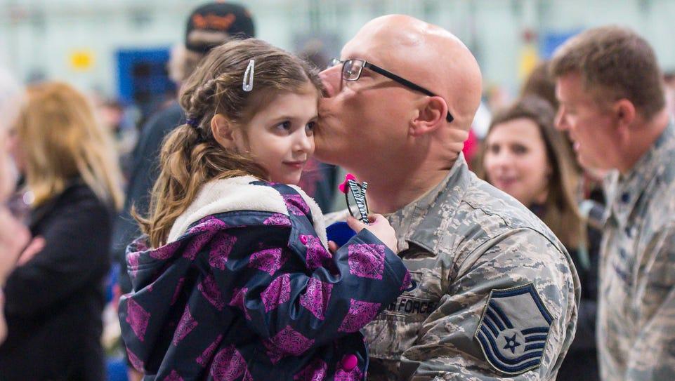 Master Sgt. Darren Adams of Milton kisses his daughter