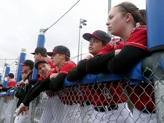 Grace Briner (right) and Ashlyn Hanson (second from right) join the rest of the Crosspoint baseball team in the dugout at Gene Lobe Field.