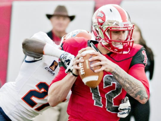 Western Kentucky Hilltoppers quarterback Brandon Doughty (12) is sacked by UTEP Miners defensive back Devin Cockrell (27) during the Hilltoppers' 35-27 victory over UTEP in the homecoming NCAA college football game at Houchens Industries-L.T. Smith Stadium on Saturday, Nov. 8, 2014, in Bowling Green, Ky. (AP Photo/Daily News, Austin Anthony)