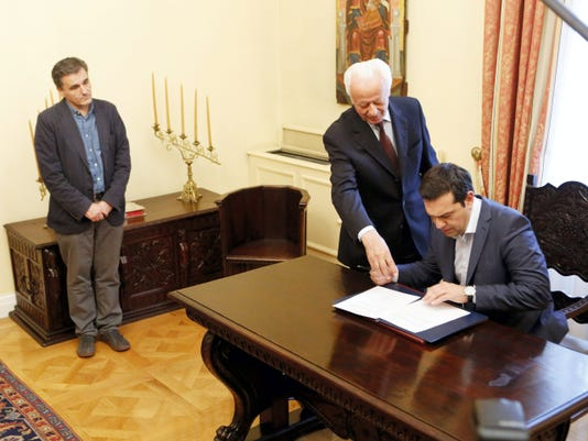 Greece's Prime Minister Alexis Tsipras, right, signs a protocol as the new Greek Finance Minister Euclid Tsakalotos, left, looks on during the swearing in ceremony at Presidential Palace in Athens, Monday. Following Sunday's referendum the Greece and its membership in Europe's joint currency faced an uncertain future Monday, with the country under pressure to restart bailout talks with creditors as soon as possible after Greeks resoundingly rejected the notion of more austerity in exchange for aid.