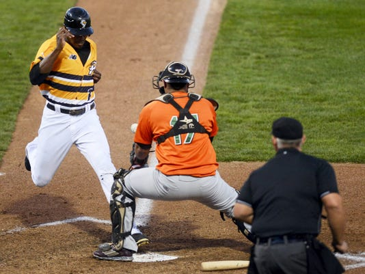 The York Revolution's James Simmons, left, beats the tag by Long Island Ducks catcher Alex Marquez to score during the second inning of Wednesday's game at Santander Stadium in York. The Revs plated six runs in the second inning and earned a 10-3 victory.
