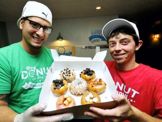 Bill Kalathas, left, and Brandon Bless display donuts at their new Chambersburg shop, Tuesday, Oct., 27. The Doh-Nuh T Company, located beside Texas Lunch on Lincoln Way West, offers made-to-order donuts with 13 different glazes and 18 topping choices.