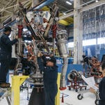 Blue Origin technicians assemble a BE-3 hydrogen engine at the company's Kent, Washington, facility. The company wil soon build rockets in North Brevard.