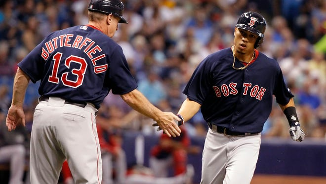 Boston Red Sox right fielder Mookie Betts is congratulated by third base coach Brian Butterfield as he runs around the bases after he hit a grand slam during the second inning against the Tampa Bay Rays at Tropicana Field.