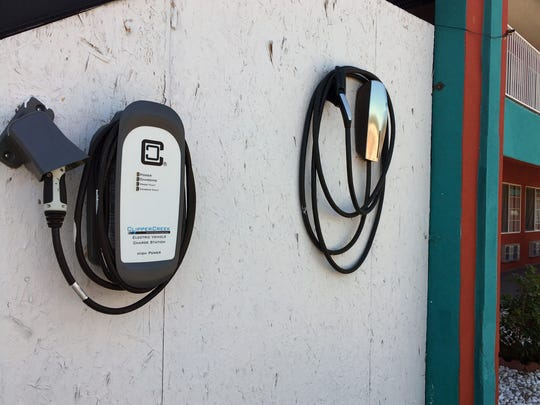 In this Wednesday, July 13, 2016 photo, a charging station is shown at the Sandia Peak Inn along Albuquerque's Route 66, in N.M. Route 66, a highway made famous for attracting gas-guzzling Chevrolet Bel Airs traveling from Chicago to Los Angeles, is seeing a growing number of electric car charging stations along the 2,500-mile path, and some states are even pushing for solar panels and electric buses.